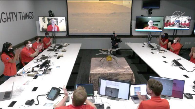 Pierwszy lot helikoptera na Marsie, widziany z pokoju kontrolnego NASA / JPL, z bezczelnym czerwonym ubraniem siedzącym wokół stołu w kształcie litery U, z wieloma ekranami i modelem helikoptera pośrodku.