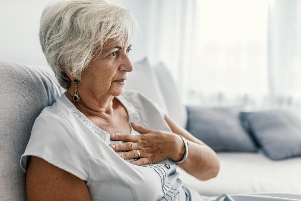 Starsza kobieta cierpi na zawał serca.  Kobieta trzymająca się za klatkę piersiową, ostry ból, możliwy zawał serca.  Choroba serca.  Pojęcie problemu z sercem
