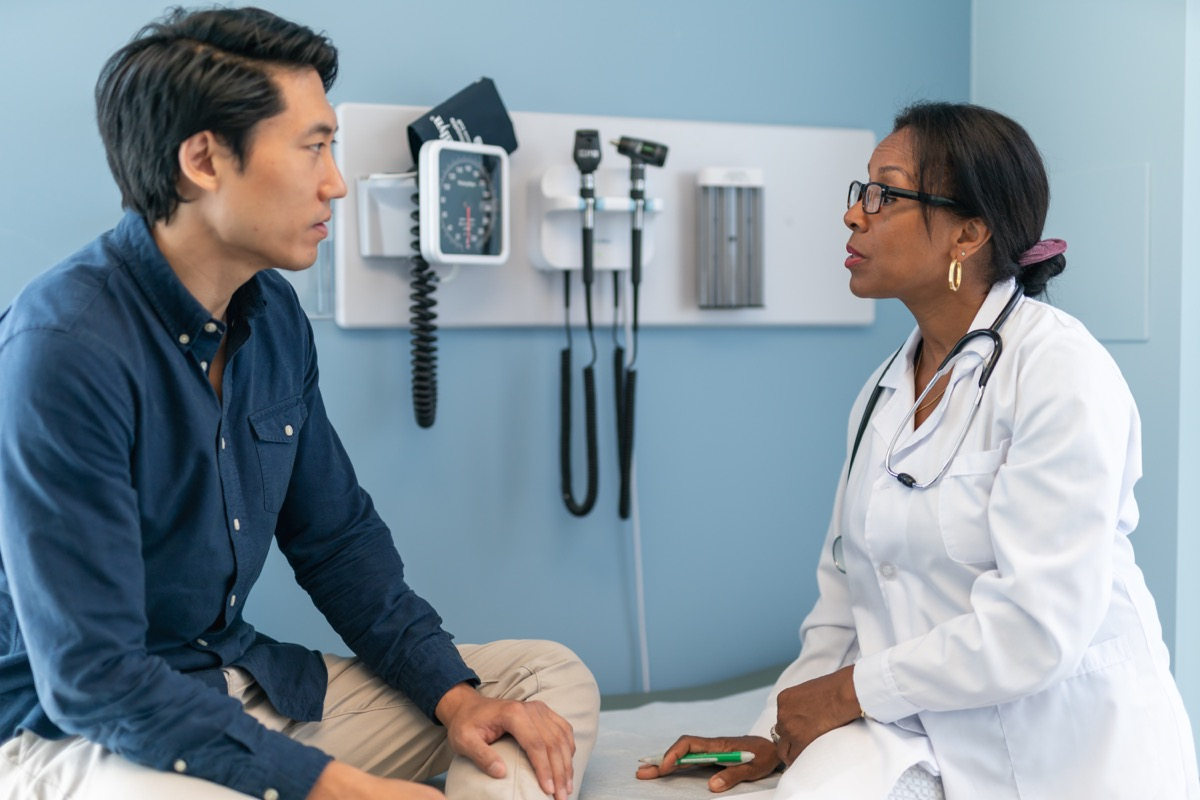 Pacjent siedzi na stole do badań w poradni.  Lekarz mężczyzny siedzi przy stole obok niego.  Dwie osoby stoją naprzeciw siebie.  Pacjent uważnie słucha rad swojego lekarza.