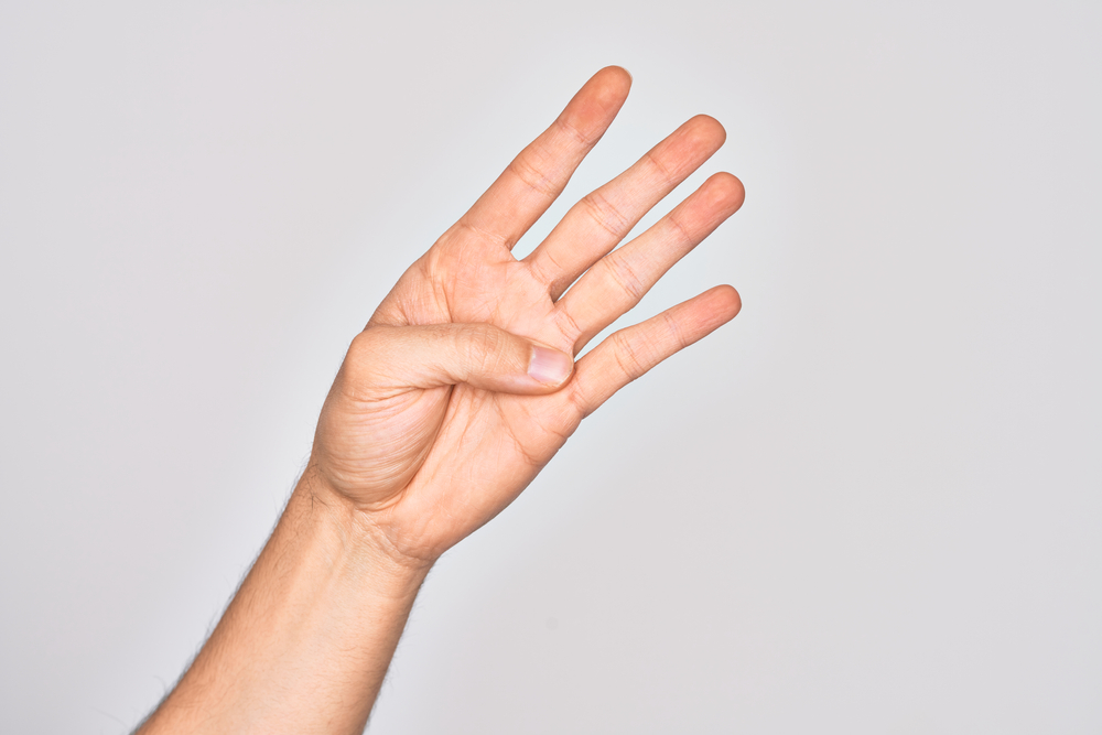 Zbliżenie dłoni z kciukiem wyprostowanym na dłoni