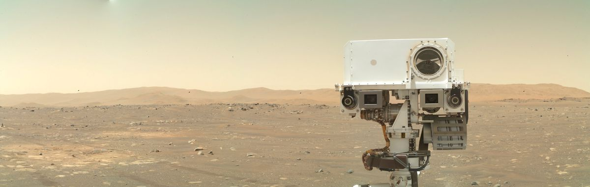 Głowa wytrwałości wystaje z dołu kadru jak twarz, przed horyzont Marsa.