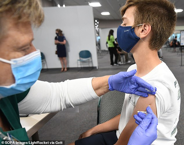 Na zdjęciu pielęgniarka podająca 13-letniemu Nicholasowi Milesowi zastrzyk szczepionki firmy Pfizer.  Niedawne badanie wykazało, że siedmiu chłopców w wieku od 14 do 19 lat zachorowało na serce po drugiej szczepionce COVID (zdjęcie pliku)