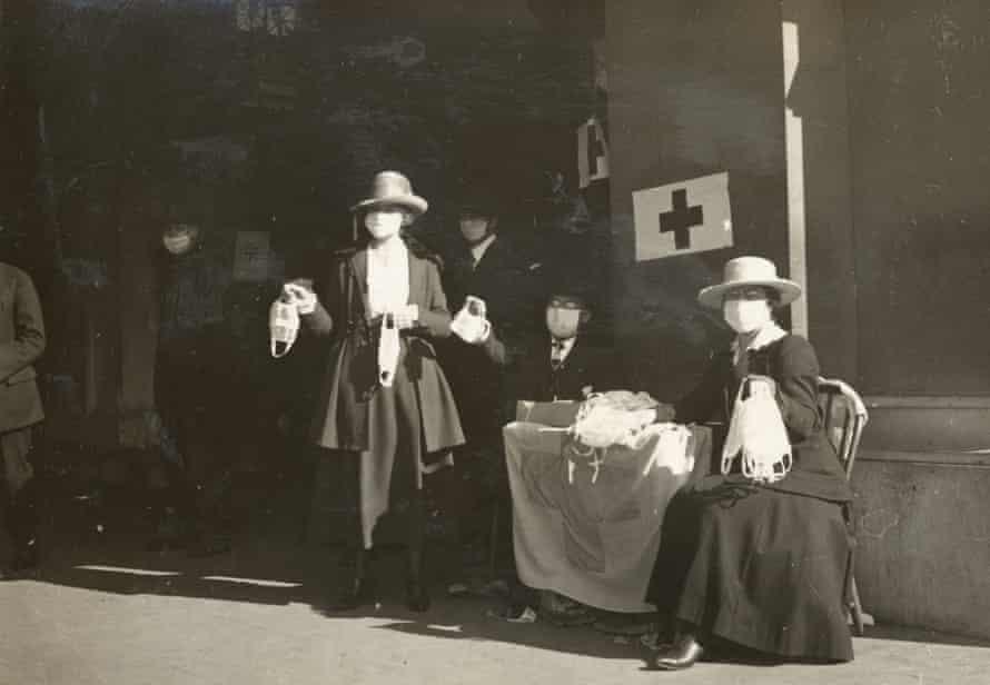 Wolontariusze Czerwonego Krzyża rozdają maski przeciw grypie przy stole w San Francisco w 1918 roku.